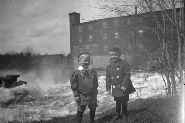 Two Children In Front Of Red Mill